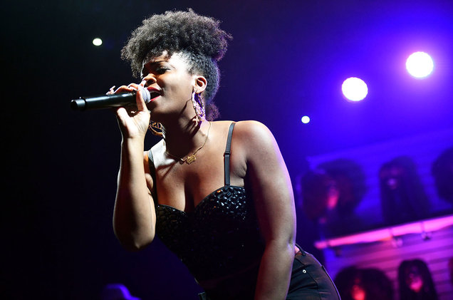 Ari Lennox in a black top with black jeans. Ari is holding a black microphone. Ari has on gold earrings and a gold necklace.