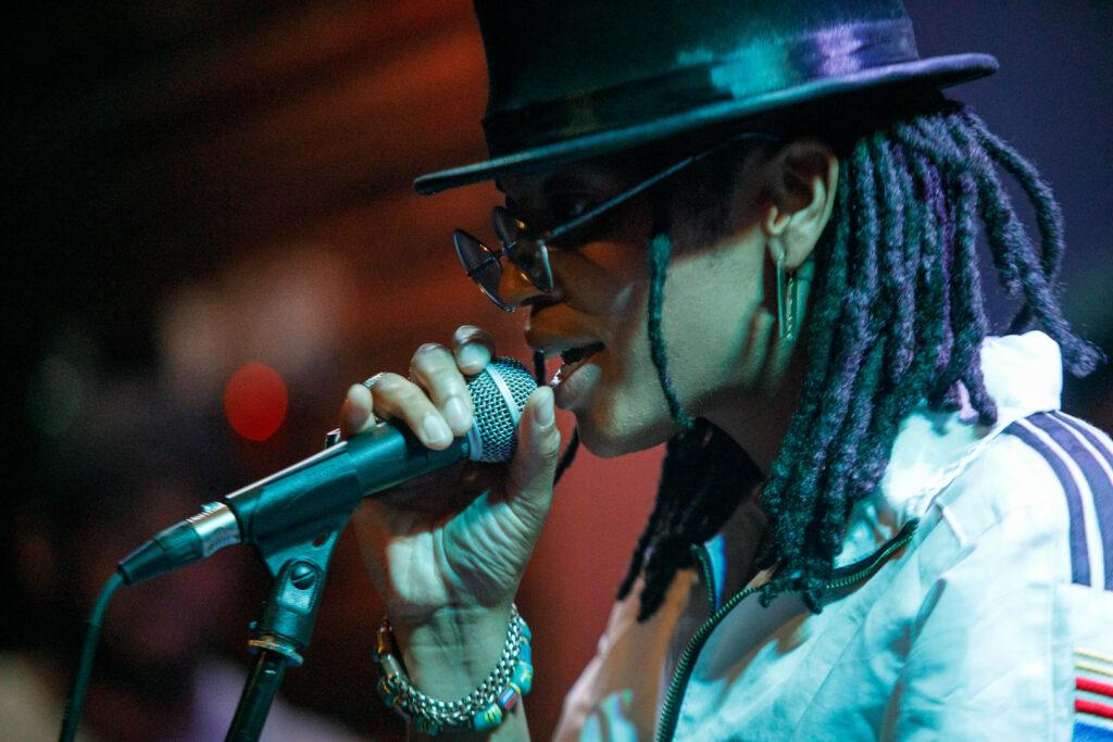 Fannie Mae singing on a black mic, wearing a black hat